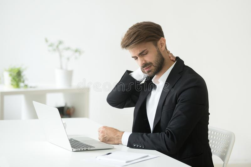 Young businessman in suit feeling neck pain after sedentary work stock photos