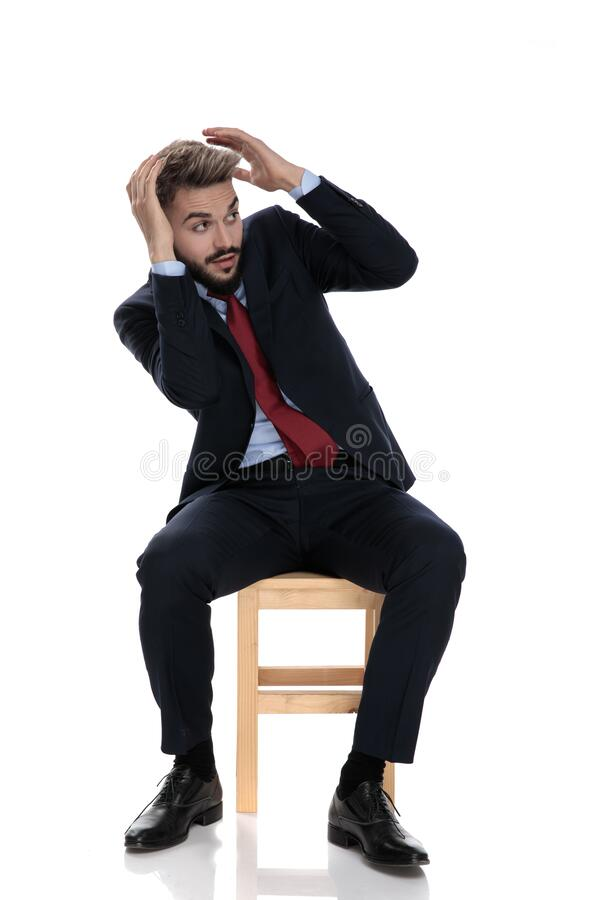 Young businessman in suit holding hands up and defending. Himself, sitting isolated on white background royalty free stock photos