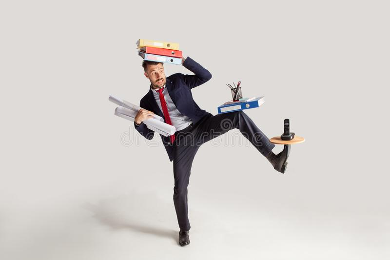 Young businessman in a suit juggling with office supplies in his office, isolated on white background royalty free stock photography