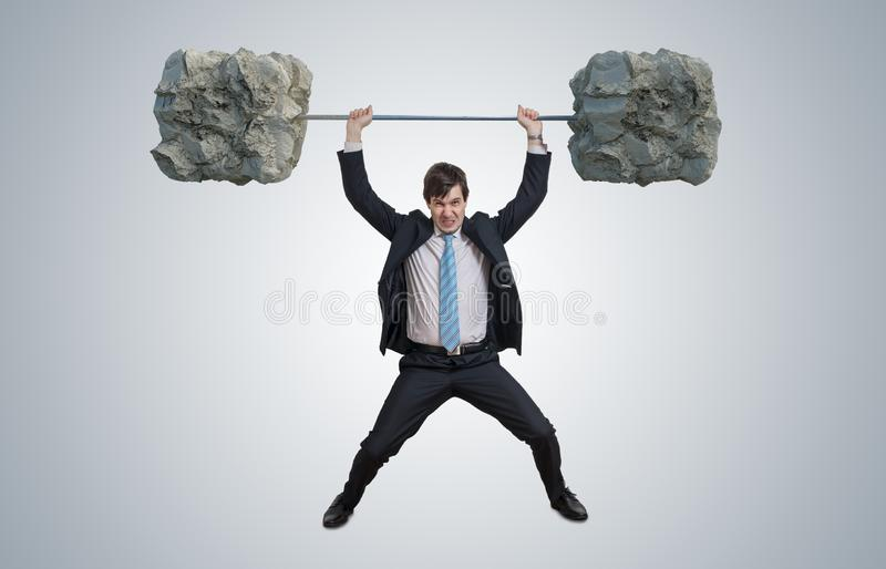 Young businessman in suit is lifting heavy weights. Young businessman in suit is lifting heavy weights royalty free stock photo