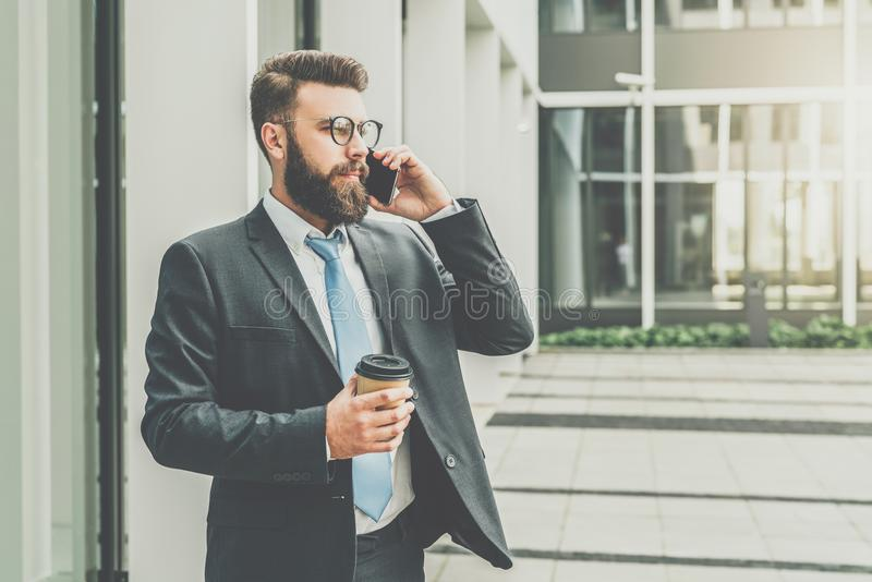 Young businessman in suit and tie is standing outdoor, drinking coffee and talking on his cell phone. stock images