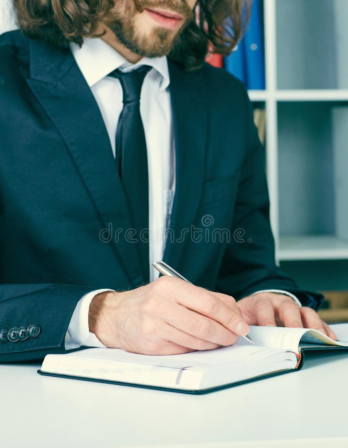 Young businessman in suit working at office, sitting at desk and writing notes for personal organizer. stock photos