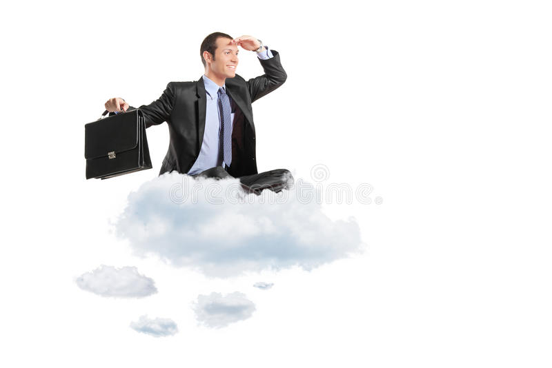 Young businessman with suitcase sitting on a cloud royalty free stock image