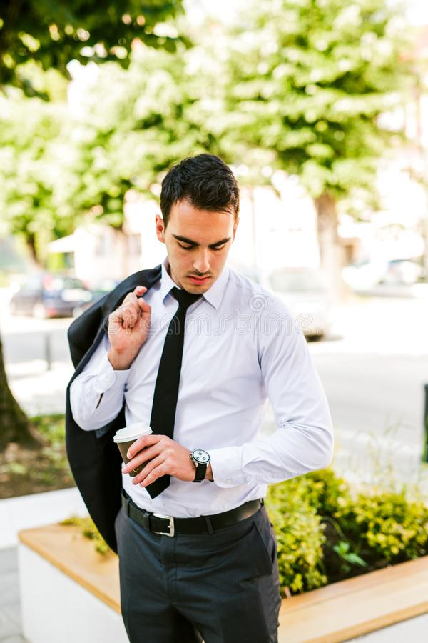 Young businessman take break to drink coffee but now looking how time is it. Young business man take break to drink coffee but now looking how time is it royalty free stock image