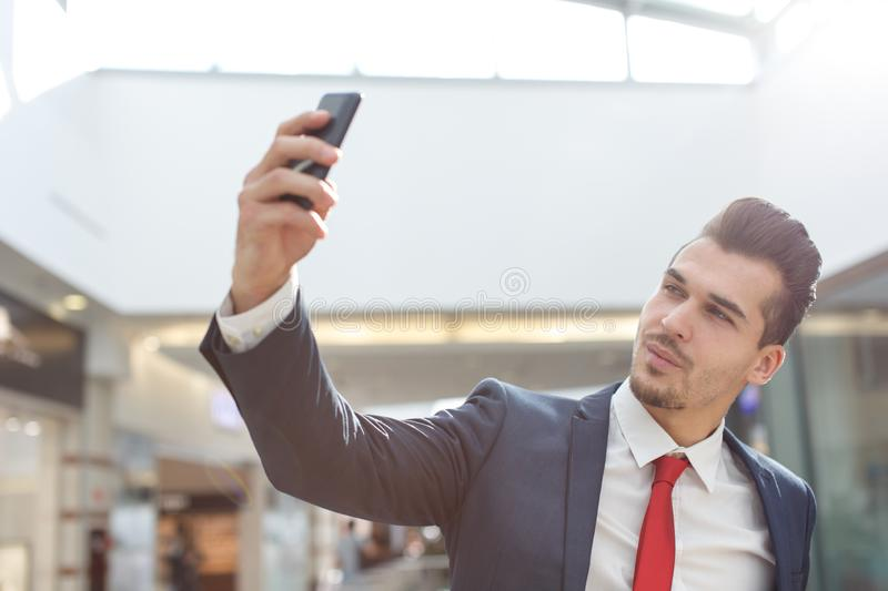 Young businessman taking selfie in business center stock photography