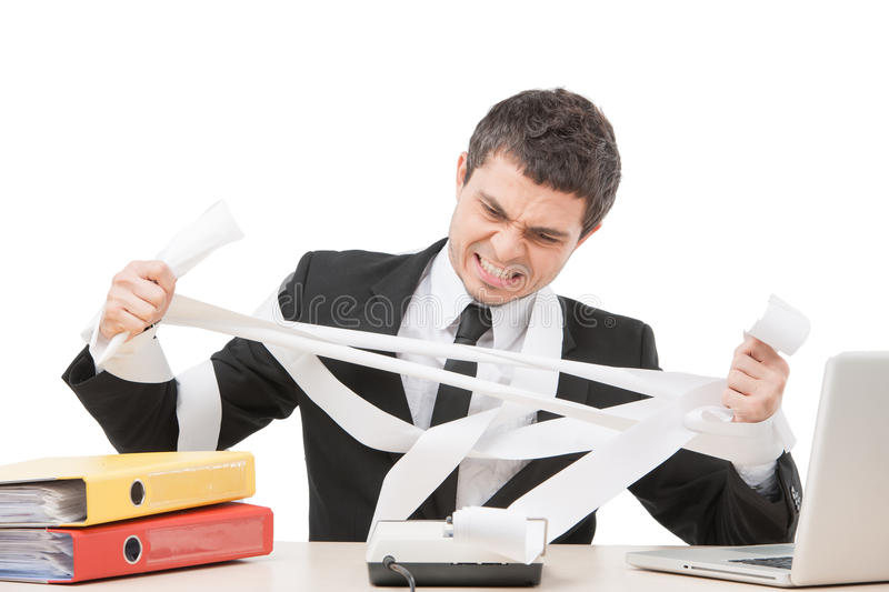 Young businessman tearing paper apart. Upset worker sitting at desk and calculating royalty free stock image