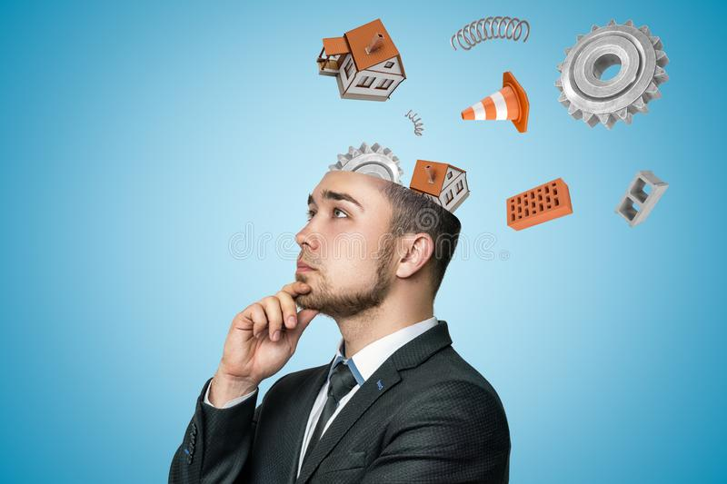 Young businessman thinking with white houses, gear wheels, bricks and traffic cone flying out of his head on blue stock photo