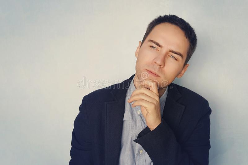 A young businessman in a thoughtful pose reflects on business. Thinking through ideas and plans. A grown guy on a blue background royalty free stock photo