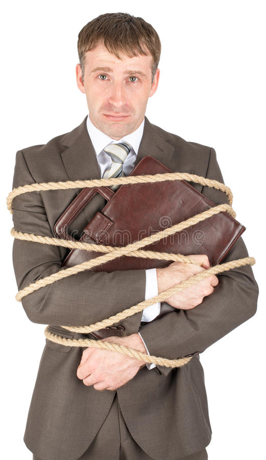 Young businessman tied with ropes royalty free stock photography