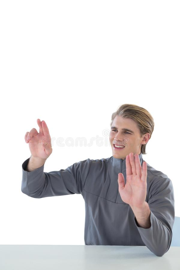 Young businessman touching imaginary interface screen while sitting at table. Against white background stock photo