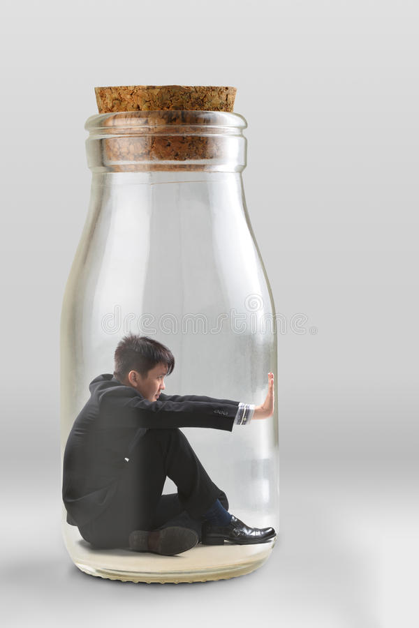 Young businessman trapped. In a glass jar royalty free stock images