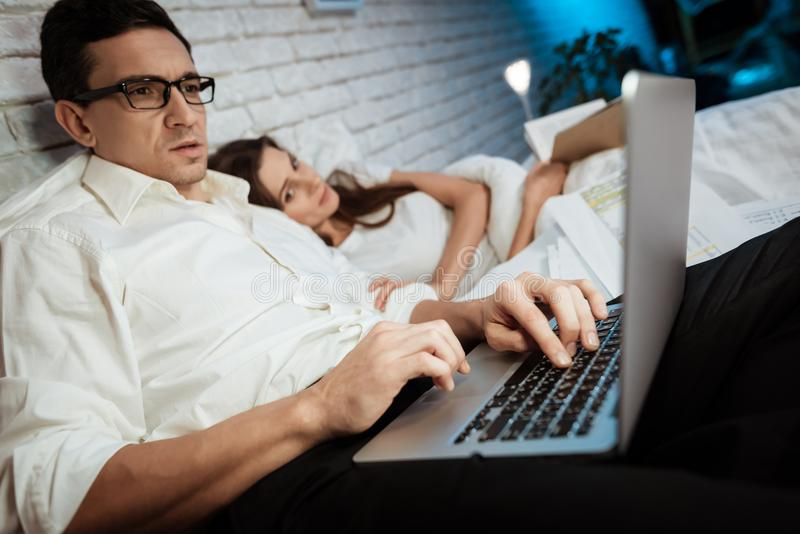 Young businessman is typing on laptop in bedroom. Woman is reading book lying in bed. stock images