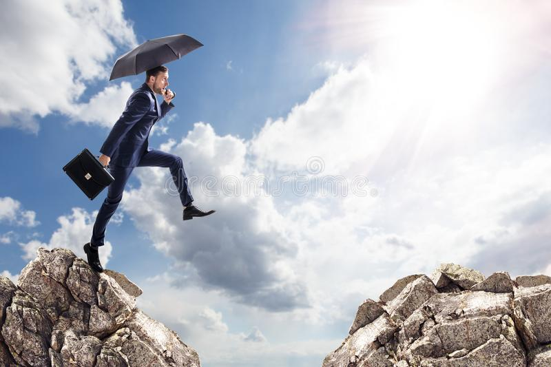 Businessman with umbrella jumping on mountains. royalty free stock photos