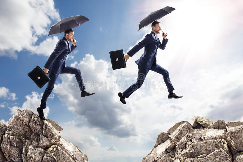 Businessman with umbrella jumping on mountains. stock image