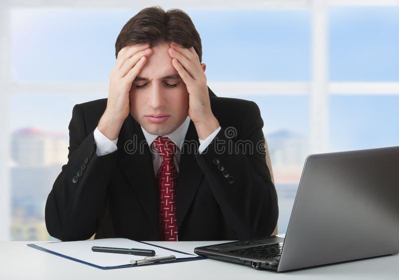 Young businessman under stress, fatigue, headache stock photography