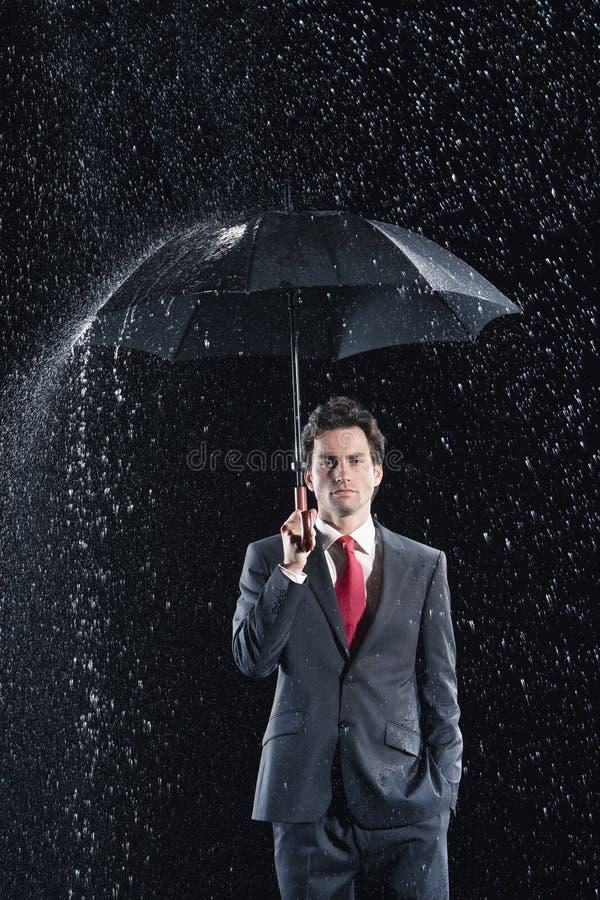 Young Businessman Under Umbrella In Rain. Portrait of a young businessman standing under umbrella in rain against black background stock image