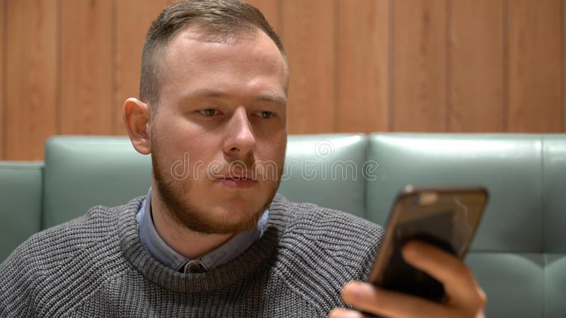 Young businessman uses social networking application on his smartphone. stock image