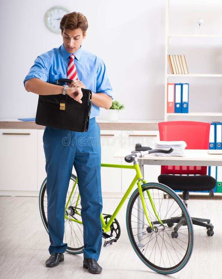 Young businessman using bike to commute to the office. The young businessman using bike to commute to the office stock photos