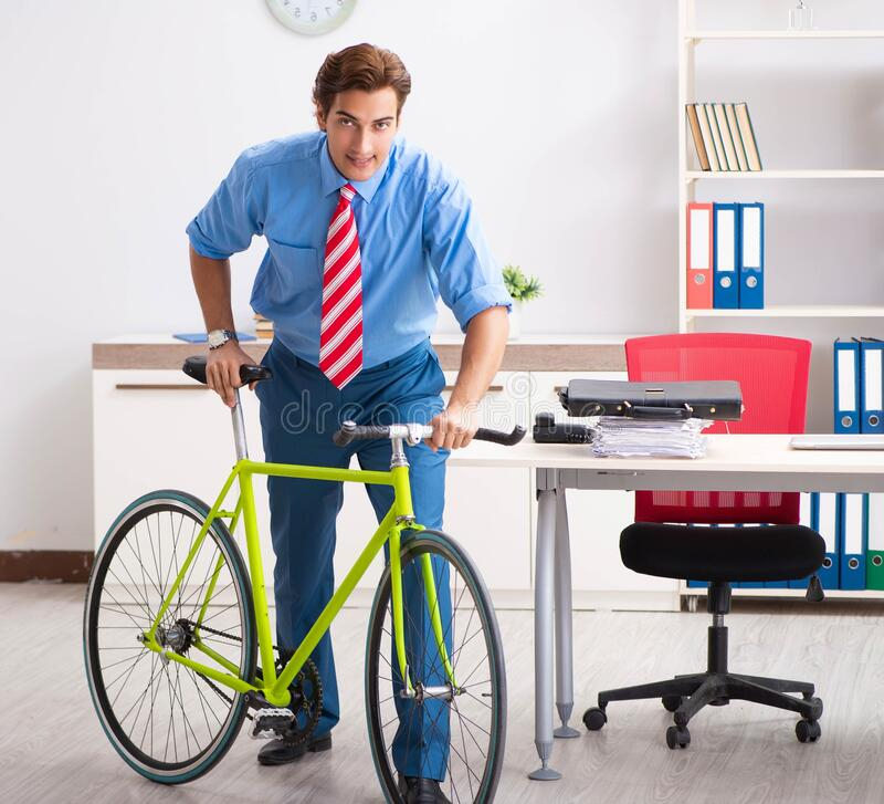 Young businessman using bike to commute to the office. The young businessman using bike to commute to the office stock photo