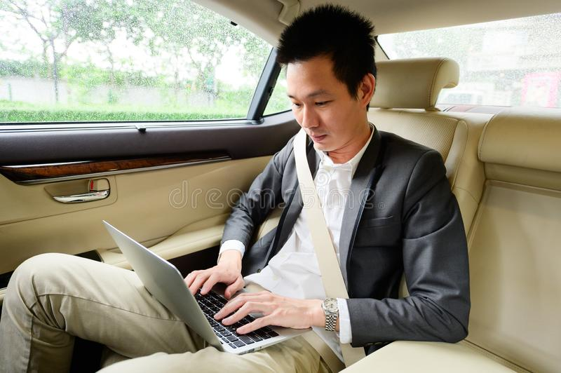 Young businessman using laptop on the backseat of a car stock image