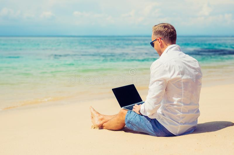 Young businessman using laptop computer on the beach royalty free stock photos
