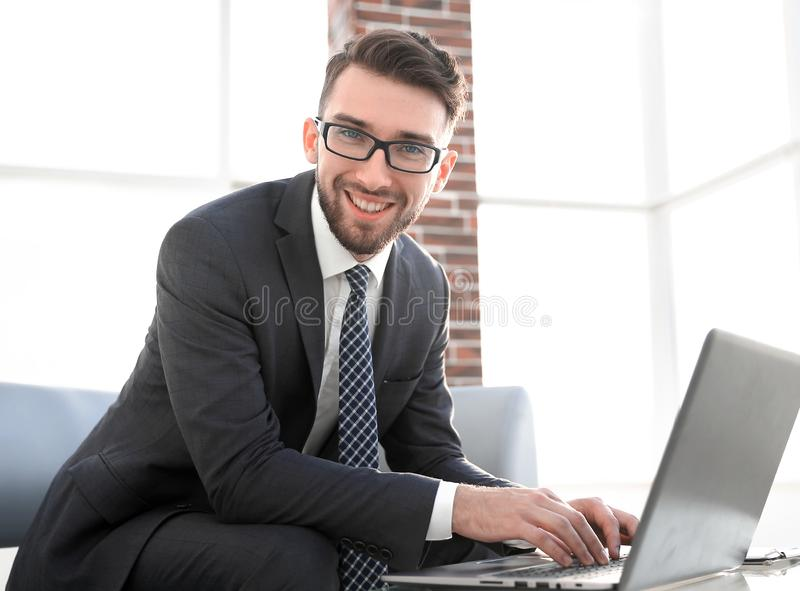Young businessman using laptop and smiling. Caucasian businessman using laptop for working at office stock photos