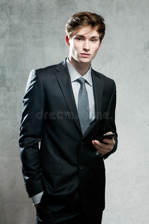 Young businessman using a mobile phone. On gray background stock images
