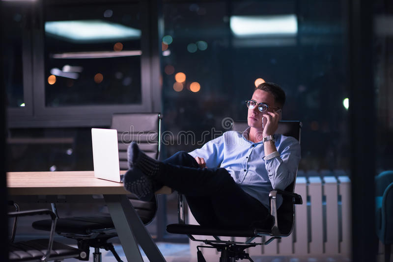 Businessman using mobile phone in dark office stock photography