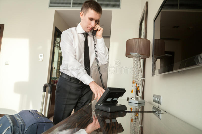 Young businessman using phone in hotel room. Young traveler businessman wearing white shirt and necktie making call after arriving in the hotel room with his royalty free stock image