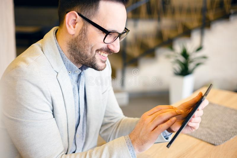 Happy young businessman using a tablet while working in a cafe stock photography