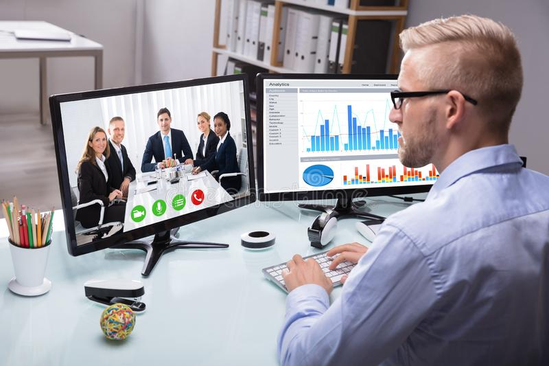 Businessman Video Conferencing With His Colleague stock image