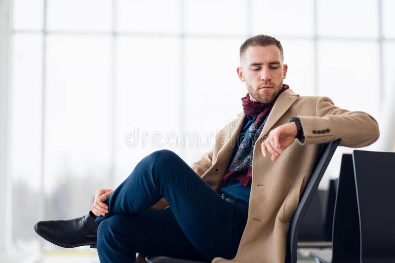 Young Businessman is waiting in the airport waiting hall and he checks the time on his watch. stock photography