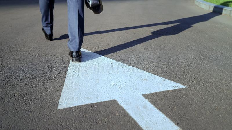 Young businessman walking along white arrow, choosing own way in life, concept stock image