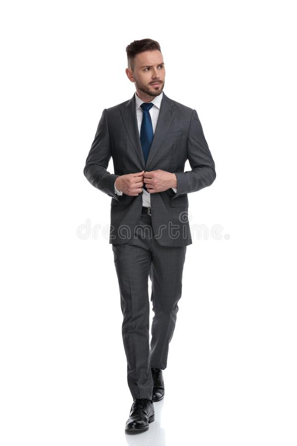 Young businessman walking and closing his coat while looking away. To side, isolated on white background royalty free stock photo