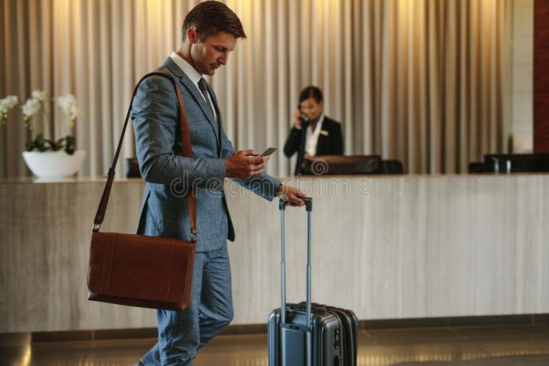 Business traveler arriving at his hotel. Young businessman walking in hotel lobby and using mobile phone. Business traveler arriving at his hotel royalty free stock images