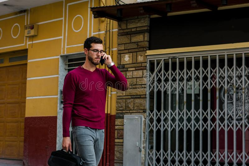 Young businessman is walking on the street while he is talking with his phone. Lifestyle, work stock image