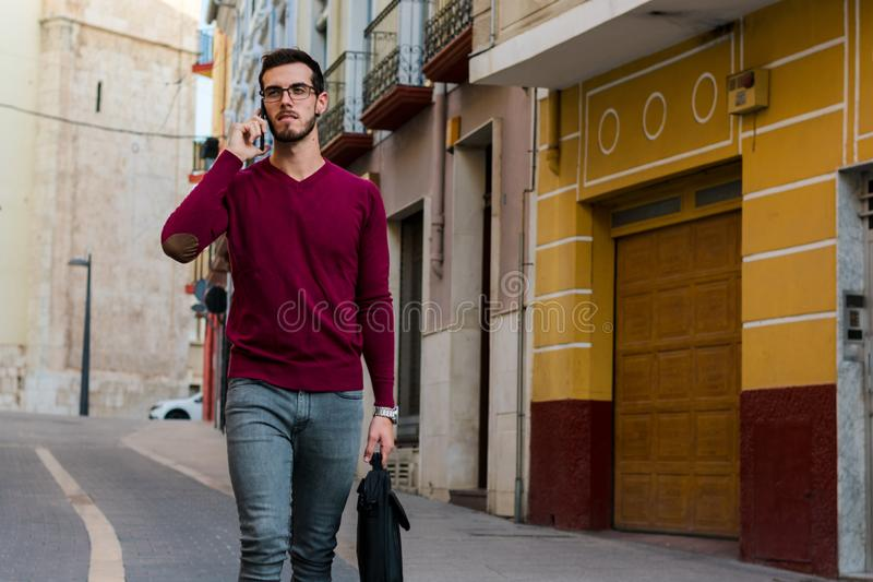 Young businessman is walking on the street while he is talking with his phone. Lifestyle, work royalty free stock photos