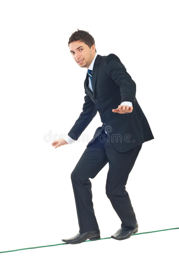 Young businessman walking on tightrope royalty free stock photo