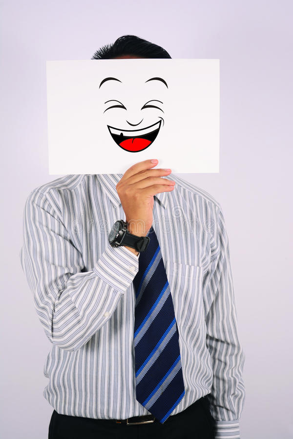 Young Businessman Wearing laugh Mask isolated on white. Businessman Wearing laugh Mask isolated on white royalty free stock images