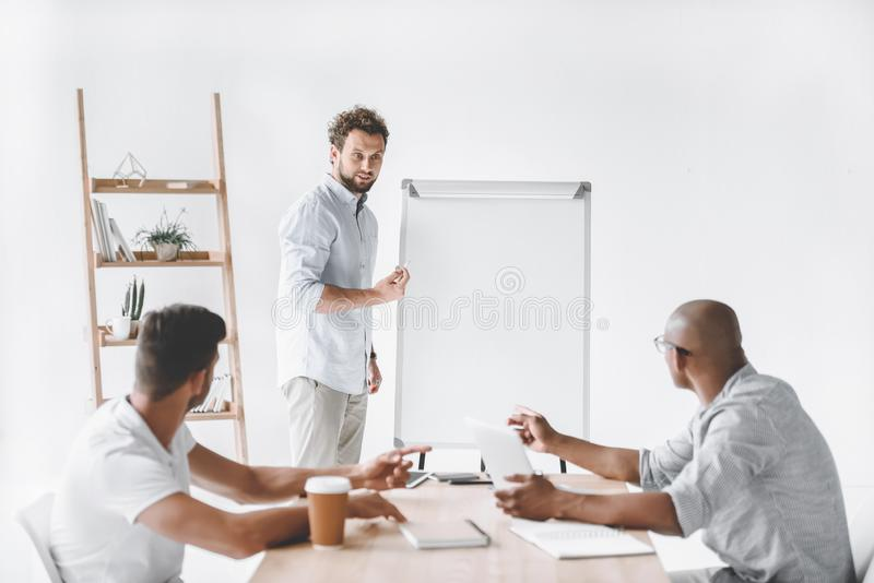 young businessman at white board making presentation stock image