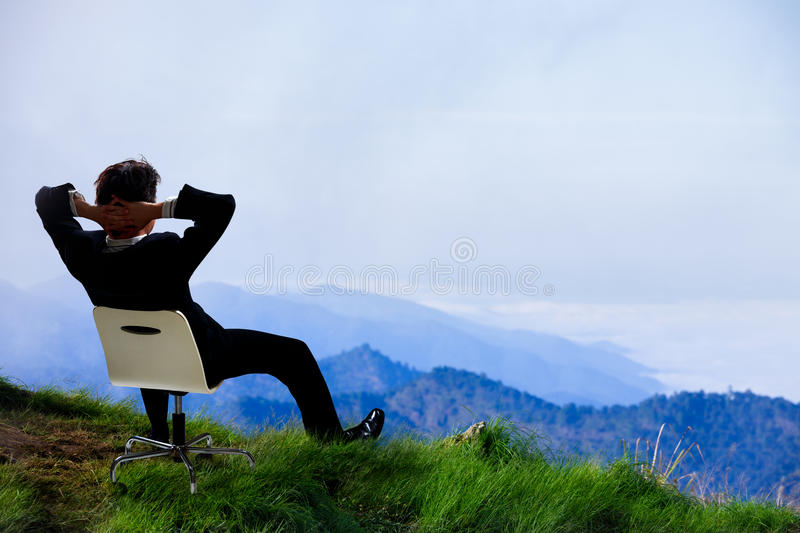 Young businessman who sits on a chair at the top of the mountain. And looks into the sky royalty free stock photography