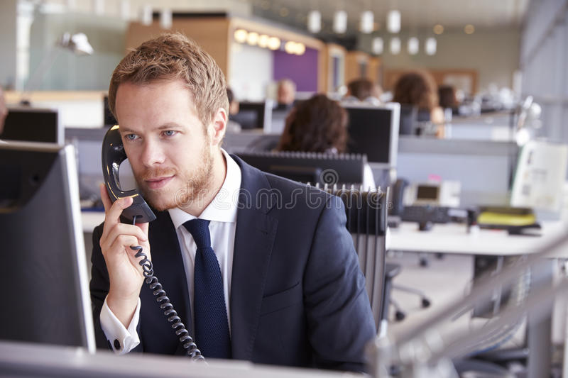 Young businessman at work in a busy, open plan office stock photos