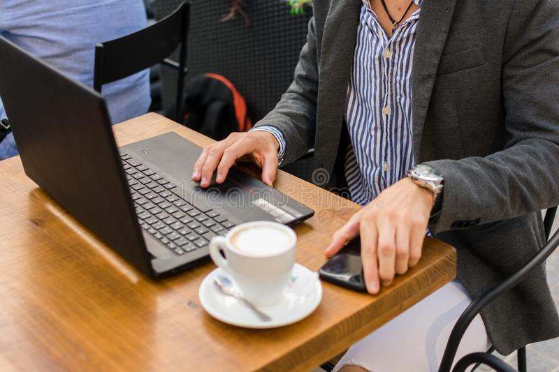Young businessman is working in a bar terrace with his laptop and smartphone. Close up stock photos