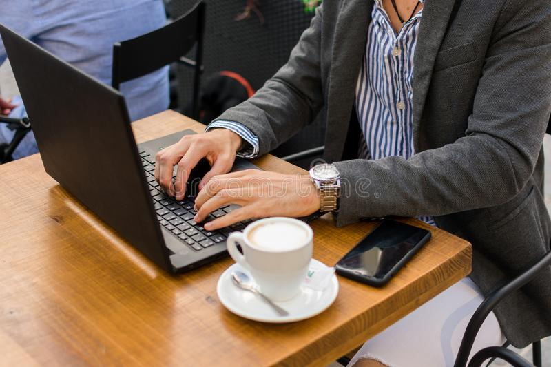 Young businessman is working in a bar terrace with his laptop and smartphone. Close up stock images
