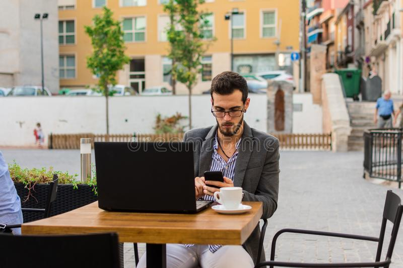 Young businessman is working in a bar terrace with his laptop and smartphone royalty free stock image