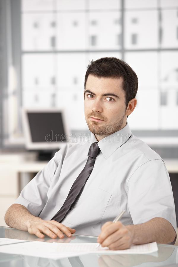 Young businessman sitting at desk writing notes stock photo
