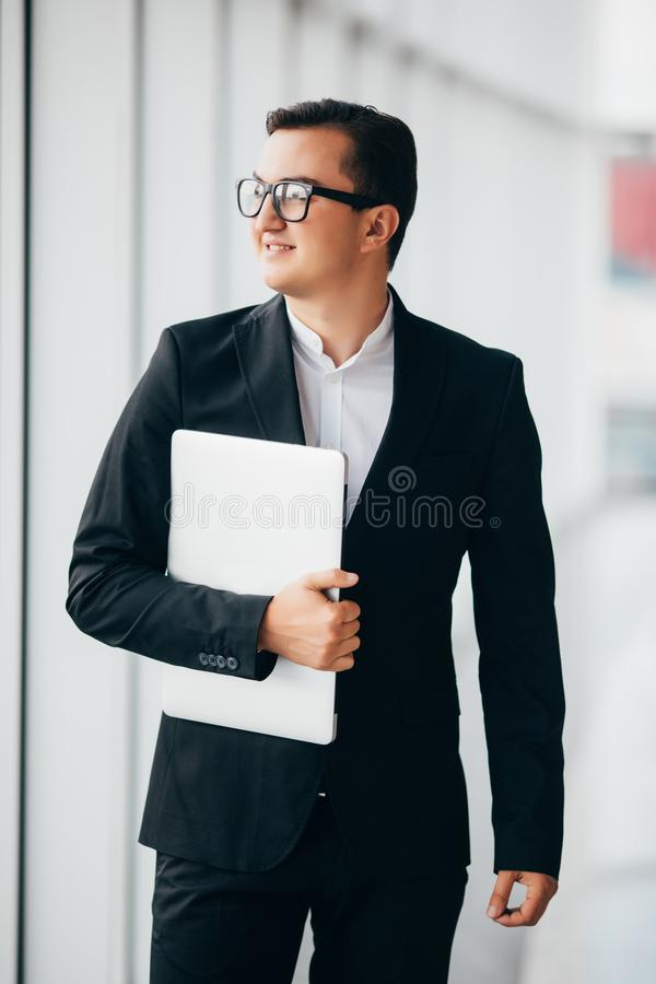 Young businessman working on a laptop computer standing in office. Man holding laptop standing near window of highrise office buil royalty free stock photo