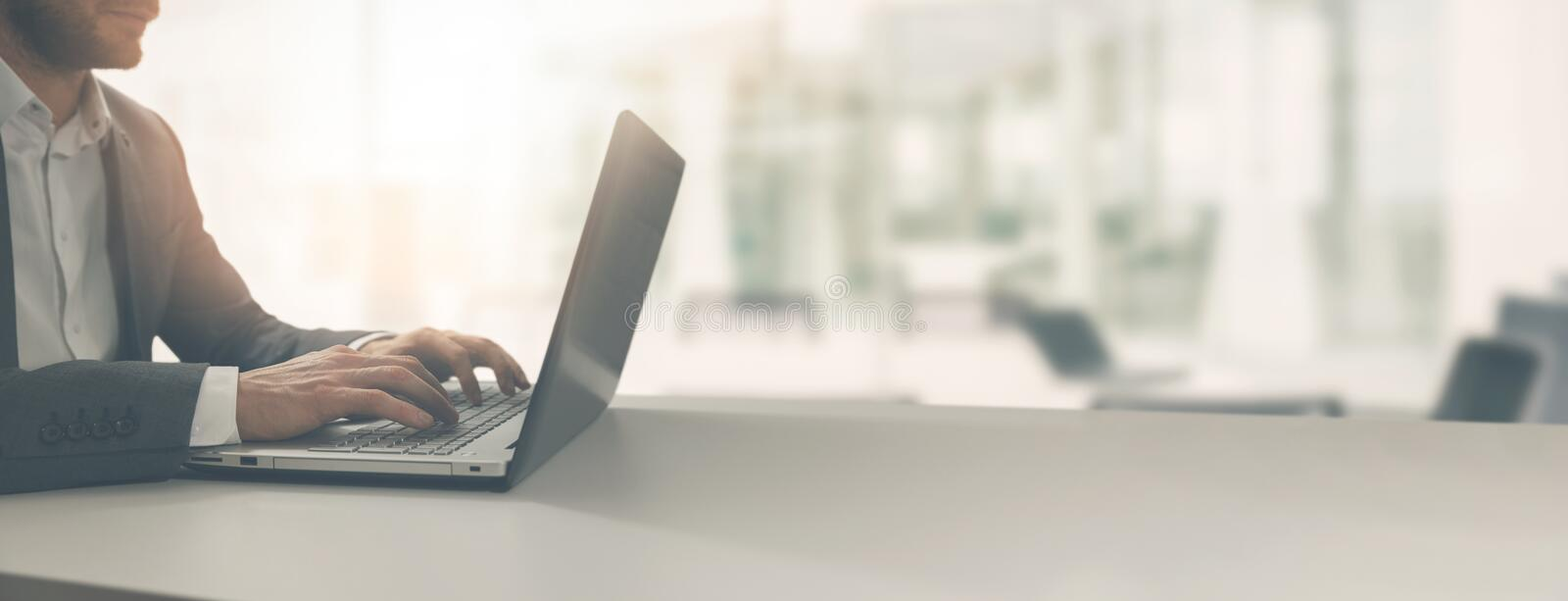 young businessman working on laptop in modern office royalty free stock photography
