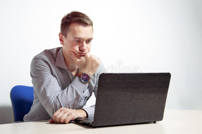 Young businessman working on laptop in office, being concerned.  stock image