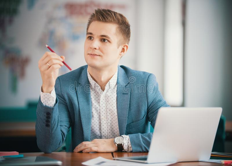 Young businessman working with laptop at office . Holding a pencil. Inspired look stock images